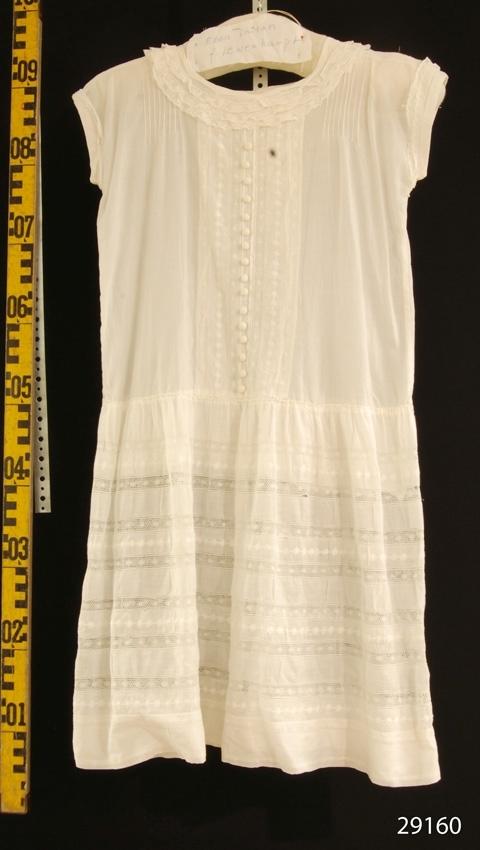 Anmärkningar: Klänning tillhört Ebba Lewenhaupt gift Linton Irsta sn Gäddeholm. Född 1913 död 2007  Barnklänning (tonårsklänning) av vit bomullsbatist med rakt liv och rynkad kjol från höften. Vit spets runt halsringningen och ärmarna. Korta ärmar. Infällda vertikala spetsar på livet och vågräta på kjolen. 16 klädda knappar på livet framtill. Tre knappar i nacken. Klänningen ihopsydd litegrann i nacken. Tvä skador fram och en bak där spets lossnat lite från tyget.