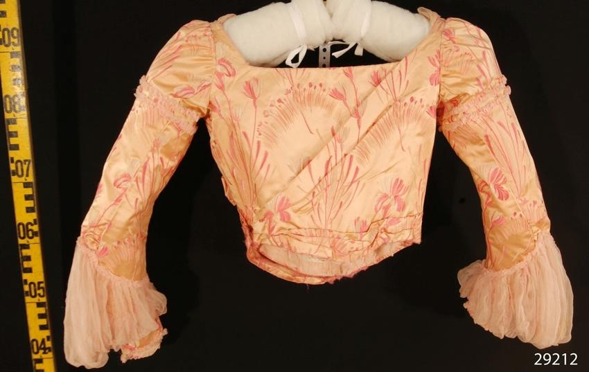 """Anmärkningar: Irsta sn Gäddeholm Använd av Ewa Lewenhaupt född Beck Friis 1858 - 1940.  Tvådelad klänning, jacka och kjol, av laxrosa brokad med vita och skära mönster. Midjekort överdel dekorerad med små rynkade band och extra puffar på ärmarna, liksom i urringningen av rosa chiffong. Insydd korsett av bomull med stålvajrar i både ryggen och framstyckena. Överdelen knäpps med 12 hakar och hyskor på framsidan. Urringningen är över crepe georgetten försedd med ett rynkat parti av rosa chiffong. Framstyckena är även dekorerade med två stora blommor sydda av samma brokadtyg som klänningen i övrigt. En är placerad under höger axel och en i midjan på vänster sida. Märkt Augusta Lundin Stockholm på band i klänningens överdel. Vid kjol med släp och tornyr bak. Två sydda sjupa veck på framsidan av kjolen. Runt kanten i jämnhöjd med längden framtill en smal volang av rosa satin med vågklippt nederkant, bredd 50 mm. Kjolens totala längd 1650 mm. Kjolen märkt med bomullsband """"nr 8""""."""
