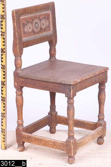 """Anmärkningar: Stol, s.k. åttaslåstol (benämning efter antalet benslåar), målad datering 1801.  Rektangulär ryggbricka med profilerade slåar upptill och nedtill. Framtill är ryggbrickan försedd med dalmåleri. Baktill står det """"Anno 1801"""" (bild 3012__c). Raka bakstolpar som är balusterformade intill sitsen. Sits av trä. Fyra fotslåar. Fyra profilsvarvade ben med runda fotavslutningar (bild 3012__b).  Enligt liggaren består invnr. 3012 av två poster. Den andra posten, en stol, finns nämnd i 2003 års inventeringsförteckning över Vallby. I samband med stiftelseupplösningen 2005 gjordes ett urval av föremålen på Vallby Friluftsmuseum, och resterande överfördes i Västerås stads ägo att användas på Vallby Friluftsmuseum. En av dessa stolar har överlåtits.  Hela stolen är av ljust lövträ utom sitsen som är av furu. Måleriet är utfört av en dalmålare. Dalfolkets arbetsvandringar är väl belagda inom forskningen. Man vet också att dalmålarna kunde röra sig på mycket stora ytor, t.o.m. till Norge och Finland. Att de tog sig ned till Västmanland råder det ingen tvekan om. Hela stolen är naturligt sliten.  Historik: Köpt från Emma Johansson, S. Salbo, Västerfärnebo sn, vid Kjellbergs besök 1924. I samband med stiftelseupplösningen 2005 gjordes ett urval av föremålen på Vallby Friluftsmuseum, och resterande överfördes i Västerås stads ägo att förvaltas av Vallby Friluftsmuseum. En av dessa stolar har överlåtits.  Negativnummer X-376"""