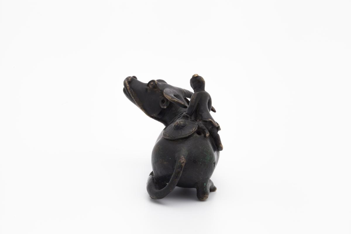 Vanndrypperen forestiller en mannsfigur som bestiger en vannbøffel. Han holder tauet festet til bøffelens mule i den ene hånden mens han løfter seg opp med den andre. Bak på ryggen ligger hatten hans, som er rikt dekorert.