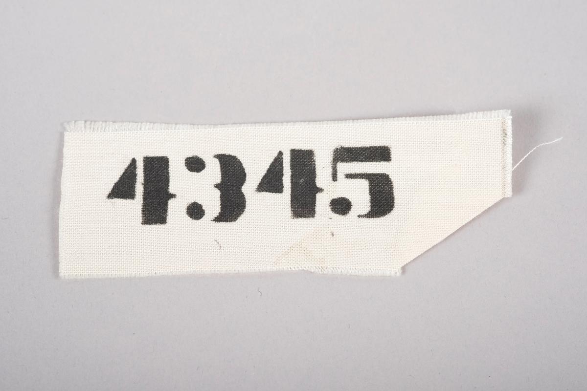 Fangenummer (4345) i svarte, trykte tall på hvitt vevet stoff.