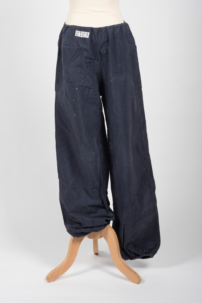 Blå bukse i vindstoff (bomull). Fargen er noe falmet. Strikk i livet og nederst i begge buksebenene. På baksiden er det påsydd en lomme på venstre buksebak. Over denne til høyre er det påsydd fangemerke. På buksens forside øverst på venstre side er det et sykke som er reparert eller lappet.