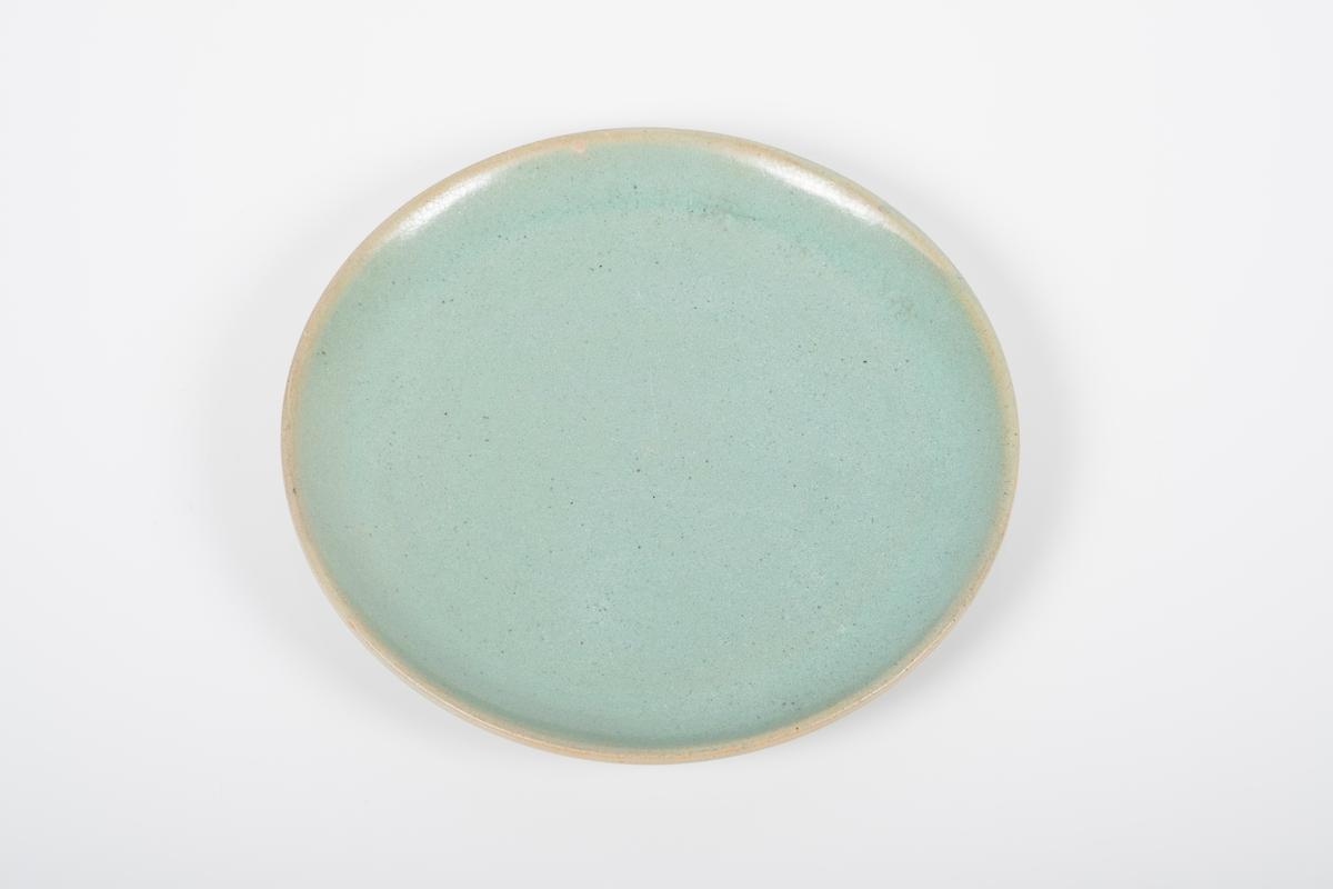 Asjett i keramikk med grønn lasur. Oversiden har blank overflate, underside (bunnen) har matt overflate. 6 små knotter på bunnen, usikker funksjon.