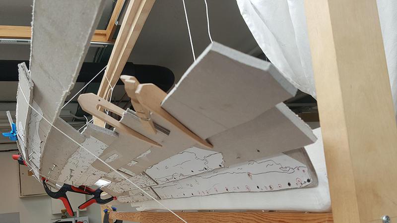 Modellen av Lovundbåten sett akter- og nedenfra. Bord i papp holdes på plass av klyper i tre og snører hengt opp i treramme.