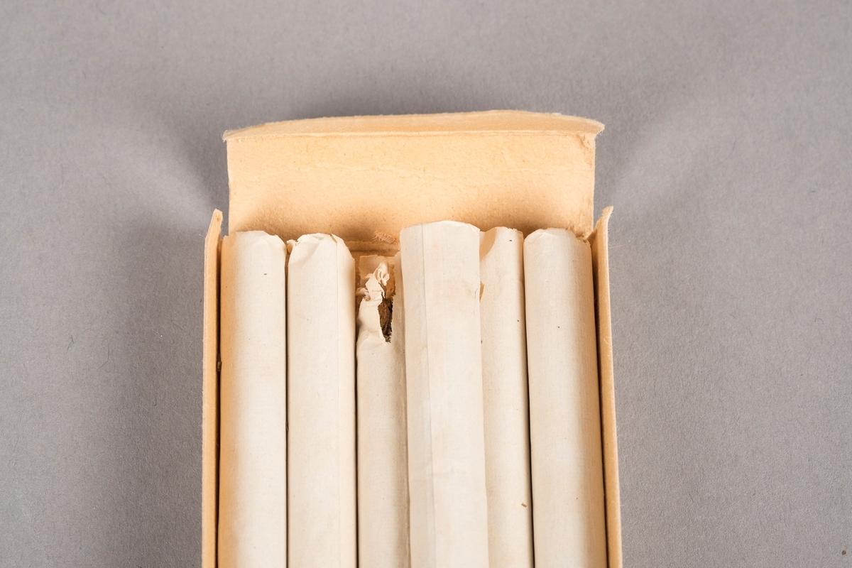 Skuff til å ha sigaretter i. Skuffen skyves inn og ut av hylsteren. Kortsidene av skuffen kan brettes ut. Skuffen er av papp. I skuffen ligger 6 sigaretter. Sigarettene er produsert ved CPC Cigaretter. Rester av lim og papir på utsiden.