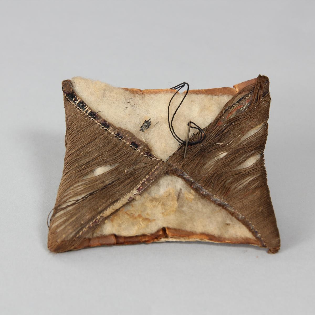 Nåldyna, kvadratisk, sydd av tygbitar. Underst vit tygbit, sedan mellanlägg och vadd/tovad bit och överst två motstående trekanter av glesa bruna trådar. Instucket nål med brun tråd.