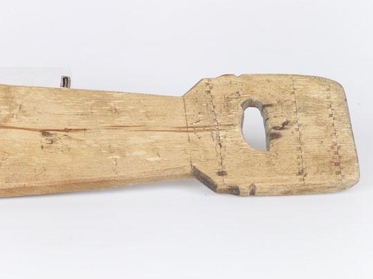 Anmärkningar: L. 708. S. Br. 110. Spolformad bräda med fyrkantiga profilerade handtag, dekorerade med fyrkantiga karvsnittsuttag i sicksackmönster. På brädans mitt en järnskodd träplatta besatt med järnpiggar. Gåva av lantbrukare Persson, Sör Rasgärde.