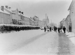 Brahegatan vintertid. Ett flertal personer i bild, vända mot