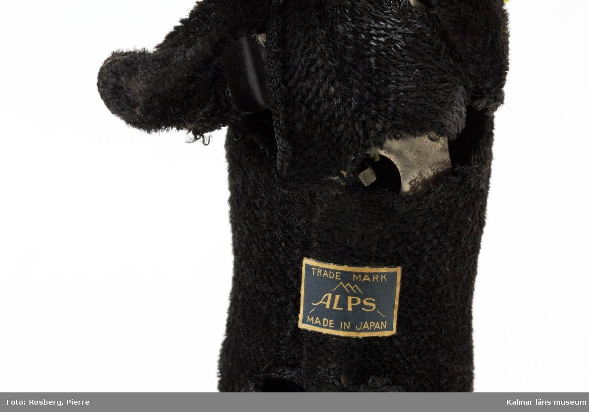 KLM 32004 Hund, leksak, metall, textil och plast ev. celluloid. Mekanisk leksakshund, svart Labrador-liknande som har ett köttben i munnen. Hunden har ett mässingsfärgat halsband. Hunden är gjord av metall med svart plysch utanpå som päls och ögon av plast. Uppdragningsmekanik med nyckel på undersidan, nyckel saknas, så att hunden kunde gå, röra på huvudet och vifta på svansen. Etikett på undersidan med texten: Trade Mark ALPS. Made in Japan.