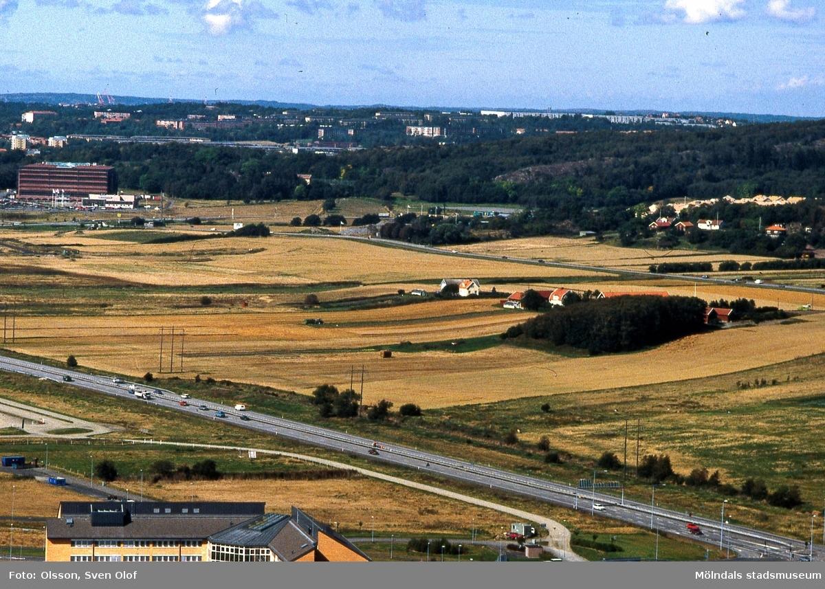 Del av Fässbergsdalen, Mölndal, i september 1993. Vy från Riskullaverkets skorsten mot Eklanda och Fässberg. I bildens nederkant ses även trafik på Söderleden. FD 6:20.