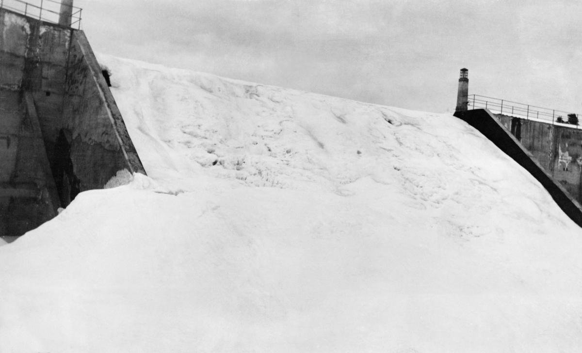 Overløpssonen på kraftverksdammen ved Osfallet i elva Søndre Osa i  Åmot kommune i Hedmark.  Fotografiet er tatt skrått nedenfra, fra en posisjon ved nordre elvebredd.  Bildet viser hvordan vannet, antakelig i svært streng kulde og på tross av et bratt fall, hadde frosset til is.  Hele damløpet var fylt av gråkvit, kjøvet is, omgitt av betongmurer, på damkrona utstyrt med stålrekkverk.  Kraftverksdammen ovenfor Osfallet ble bygd i 1913-14 med Åmot kommune som oppdragsgiver.  Samtidig ble det reist et kraftverk med to turbiner like nedenfor det til sammen drøyt 25 meter høye fallet i Søndre Osa.  Målet var å skaffe elektrisk lys til den sentrale delen av Åmot-bygda og energi til bygdas nye treforedlingsbedrift («Rena Træsliperi», seinere kalt «Rena Karton A/S»).  Kraftverket ble satt i drift i oktober 1914, men allerede i mai 1916 ble anlegget ødelagt ved et dambrudd.