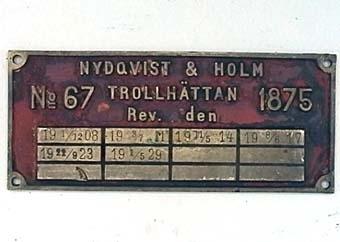 Rektangulär skylt av mässing med rödmålad botten. Skylten har tillhört UGJ ånglok nr 11, NOHAB nr 67.