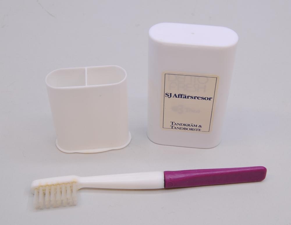 """Resetandborste i etui av vit plast med en klisterdekal på framsidan (:1) med texten """"SJ Affärsresor TANDKRÄM & TANDBORSTE"""" samt """"DENTO FRSH Thai"""". Tandborsten är i två delar. Den övre delen med borsthuvudet (:3) är av vit plast och den nedre delen (:4) av lila plast. Tandkrämen saknas. Etuiets nedre del (:2) har två fack med varsitt lufthål."""