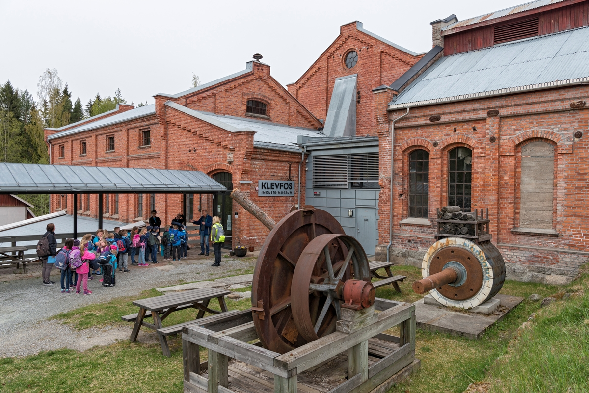 Fra Klevfos Industrimuseum på Ådalsbruk i Løten.  Fotografiet er tatt på østsida av fabrikkomplekset der museet har lagd et publikumsmottak ved inngangen til det som en gang var fabrikkens hoggeri.  I forgrunnen, under åpen himmel, står et roterende stålhjul, som ble brukt til å produsere slik flis.  Ved siden av ser vi et slipeapparat, brukt til å produsere tremasse.  Foran inngangen til museet ser vi elever fra 2. trinn ved Stavsberg skole i Furnes (Ringsaker kommune) foran inngangen til museet.  Klevfos-fabrikken ble etablert i 1888.  Den bebyggelsen vi ser her ble oppført etter en brann i 1909.  Fabrikken var i drift fram til 1976, og den ble gjenåpnet som museum ti år seinere.