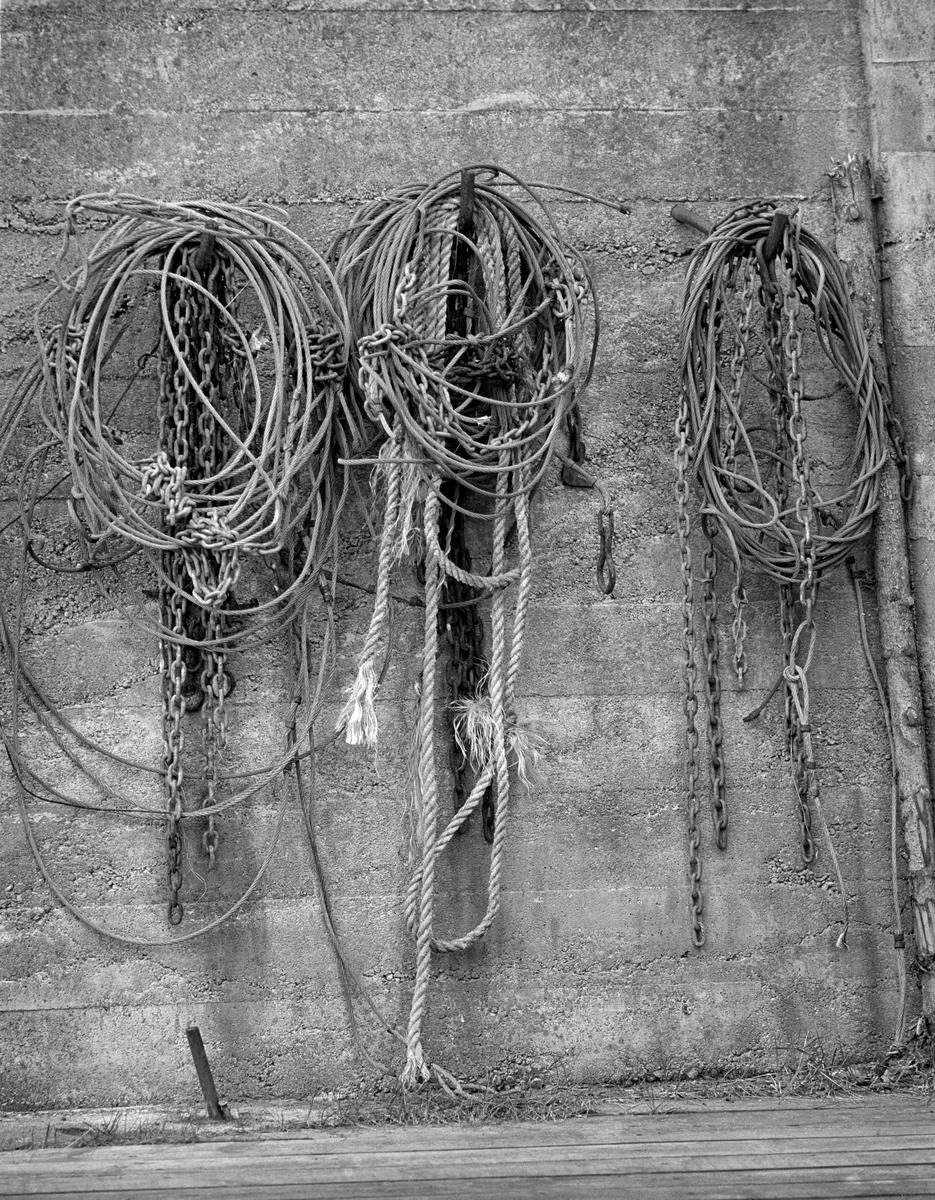 Betongmur med diverse opphengte vaiere, kjettinger og tau til bruk i forbindelse med slusedrift.  Motivet er sannsynligvis fra Strømsfoss sluse.  En liten historikk om tømmerfløting og kanaliseringsarbeid i Haldenvassdraget finnes under fanen «Opplysninger».