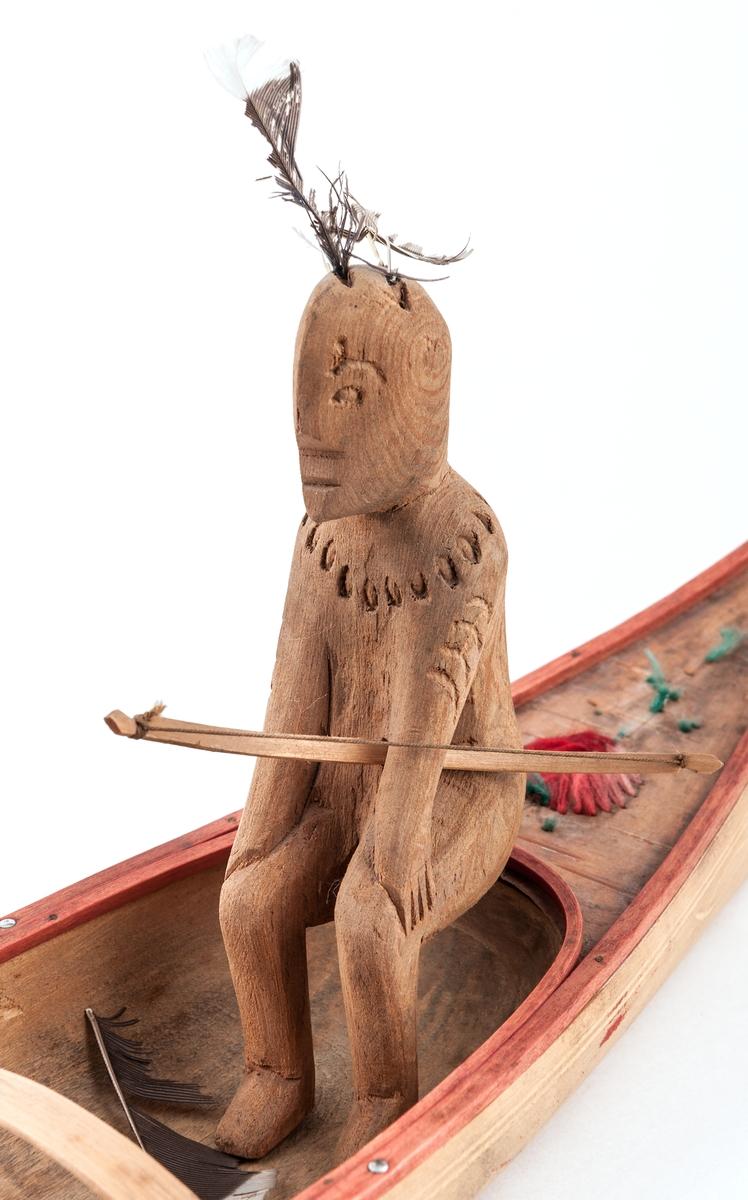 Båtmodell, kanot med indiankvinna och -man, två lösa paddelåror.