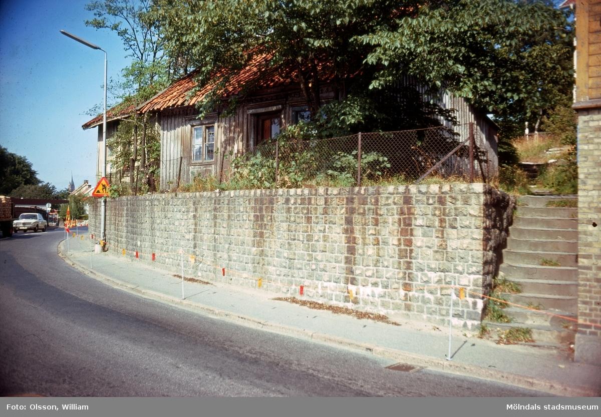 En trottoar och en stenmur som ligger utmed Kvarnbygatan 29 och 31, okänt årtal. I början av muren finns en trappa (Finketrapporna) som leder upp till ett par småhus omgivna av lummiga träd.