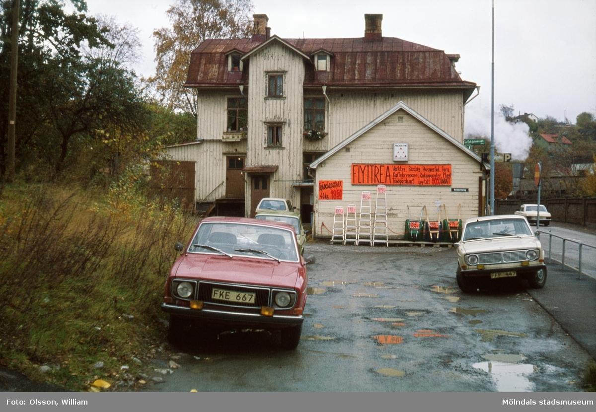 Johanssons Järnhandel på Kvarnbygatan 27, okänt årtal. Ett illa medfaret hus med fyra bilar parkerade utanför. På husets fasad sitter röda skyltar med FLYTTREA uppsatta. Nedanför skyltarna står stegar och skottkärror uppställda mot väggen. Mittemot huset, på andra sidan Kvarnbygatan, ses Papyrusområdets mur.
