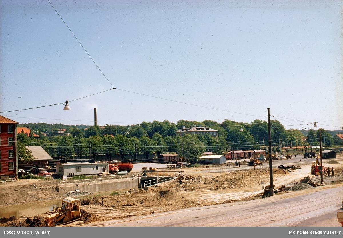 """Vy från Folkets hus mot ost, okänt årtal. Till vänster skymtas Svalövsbolaget (röd byggnad). Mark schaktas mellan Göteborgsvägen och Mölndals järnvägsstation för nybyggnad av motorvägen E6/E20. Huset i bildens mitt byggdes under 1930-talet och kallades för """"Mölndals skyskrapa"""", Kvarnbygatan 1 (numera Nämndemansgatan 1)."""
