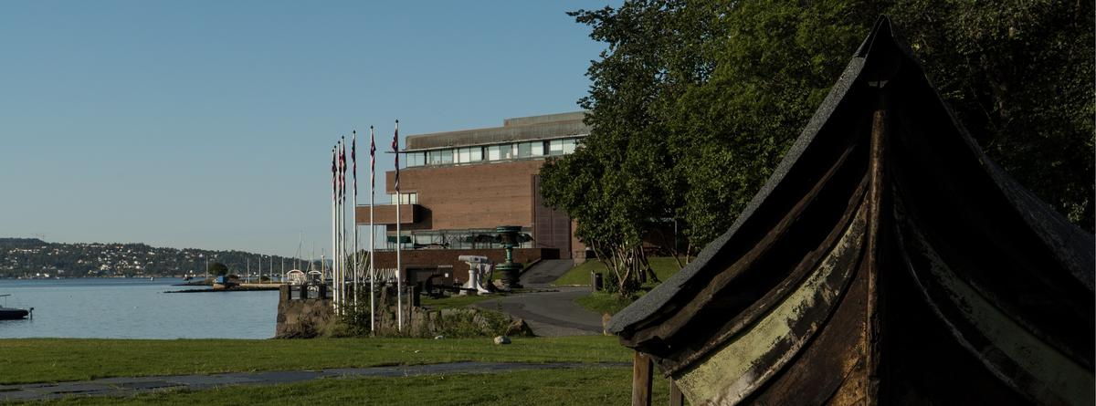 Uteområdet, museumsbygningen i bakgrunnen, et fartøy i forgrunnen.