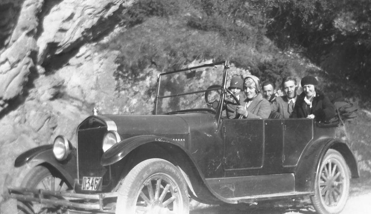 Mange personer i en gammel bil, ute på tur. D-3467