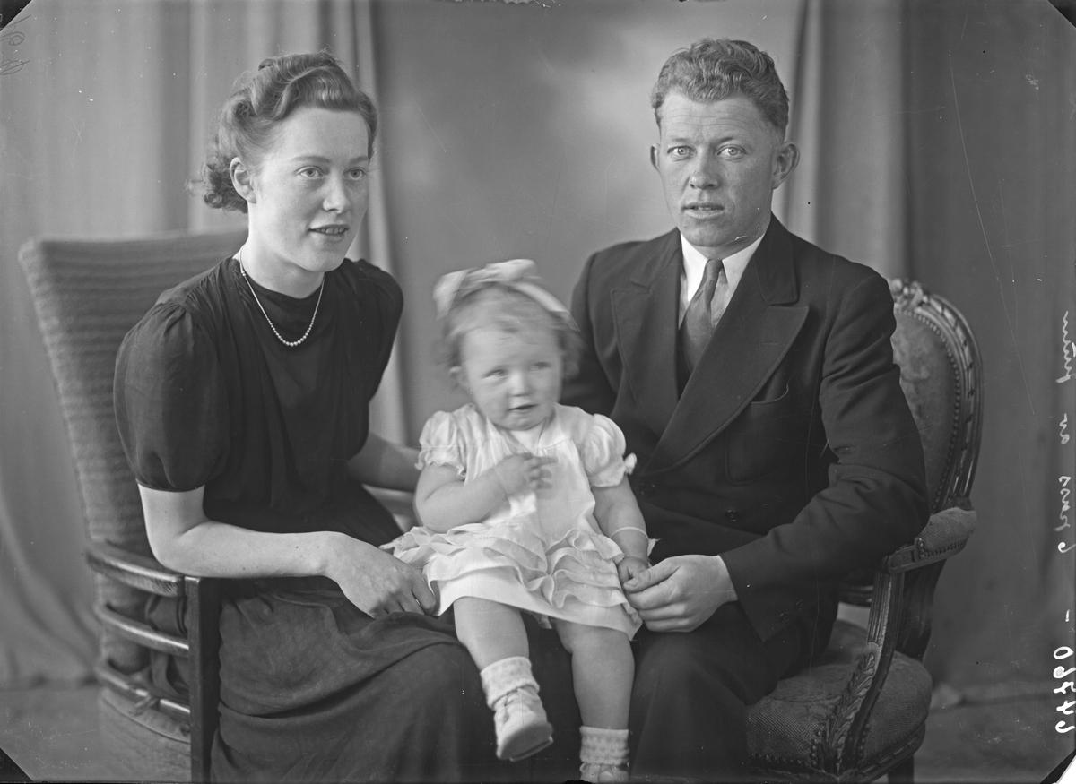 Portrett. Familiegruppe på tre. Ung kvinne, ung mann og liten pike. Mor, far og datter. Bestilt av John Mathiassen. Øvregt. 64