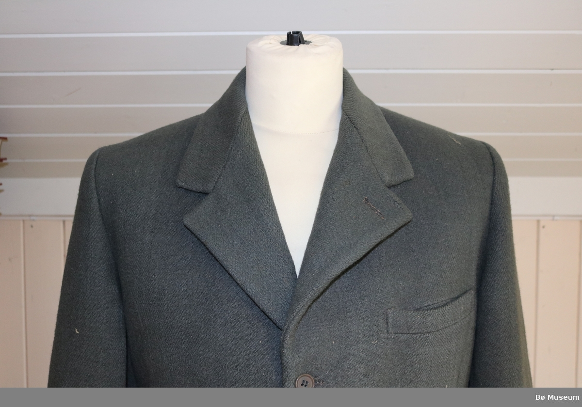 Mannsdrakt i ull. Består av nikkers (a), jakke (b), og bukseseler (c).  Nikkersen har to sidelommer, tre knappar i gylfen, og seks knappar på innsida av linninga som er til å feste bukseselene i. Spenne og reim ved knesplitt. Skjøt i skrittet, sydd ned med maskin. To baklommer med ein knapp. Alle lommene er fora og passepoilerte.  Jakka er enkeltspent, med tre knappar framme. To sidelommer, ei ytre og ei indre brystlomme. Den ytre brystlomma er passepoilert. Jakka og lommene er fora. Fire knappar nederst på ermene. Bukseselane er elastiske med skinnstroppar og har loddrette striper i mønsteret. Metallfeste mellom sele og stropp.