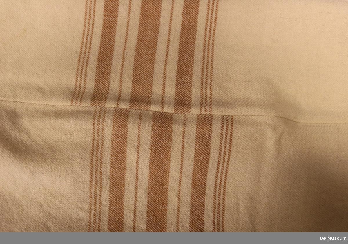 Stripete ullteppe, heimevevd og håndsydd. Sydd saman av to like store stykke. Innslag i kortsidene. Brodert L i korssting i det eine hjørnet. Litt slitt.