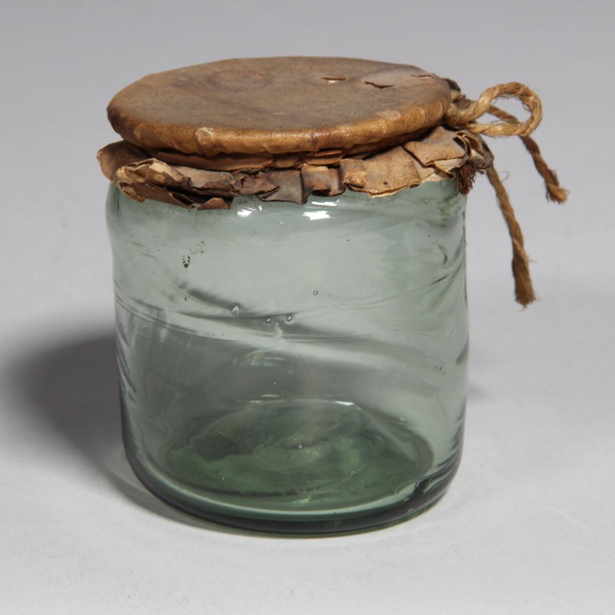Burk av grönt glas, cylindrisk med överbundet lock av papper med snöre.
