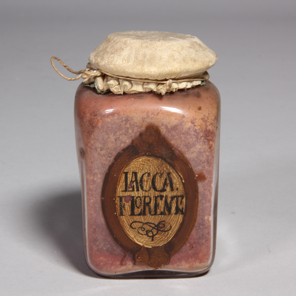 Burk av klart glas, kvadratisk med runt överbundet lock av skinn fäst med snöre. Innehåller rosa pulver.