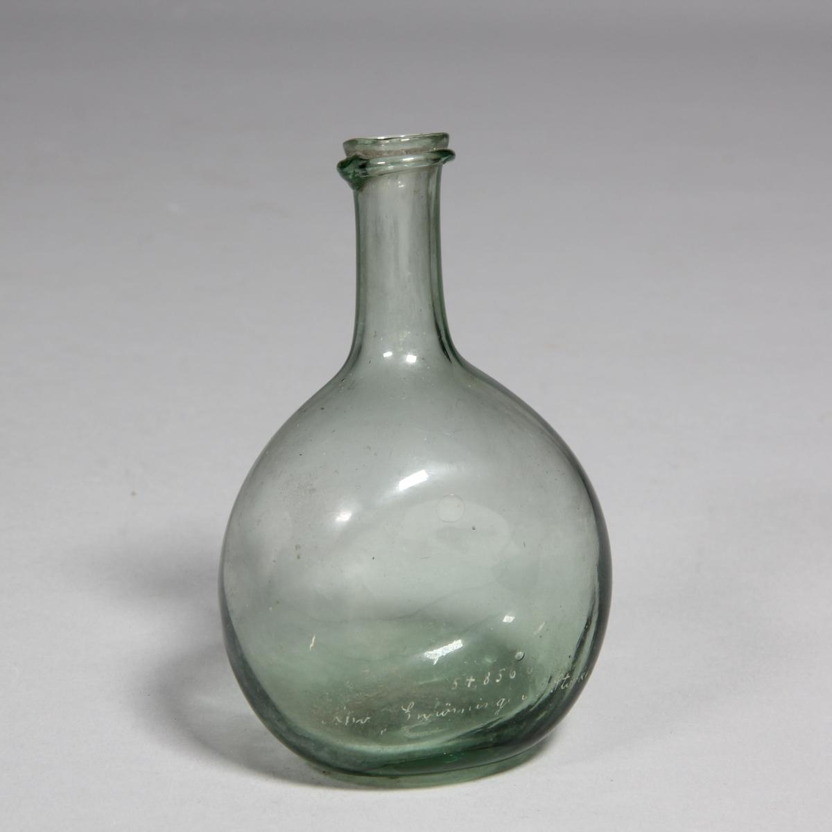 Flaska av grönt glas, rund med tillplattade sidor, lång hals.