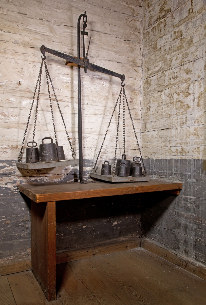 Balansvåg av järn, svartmålad, med två plattor för vikter av trä upphängda vardera med fyra järnkedjor. 8 järnvikter med handtag av olika tyngd. Monterad i vägg och på underrede av trä.