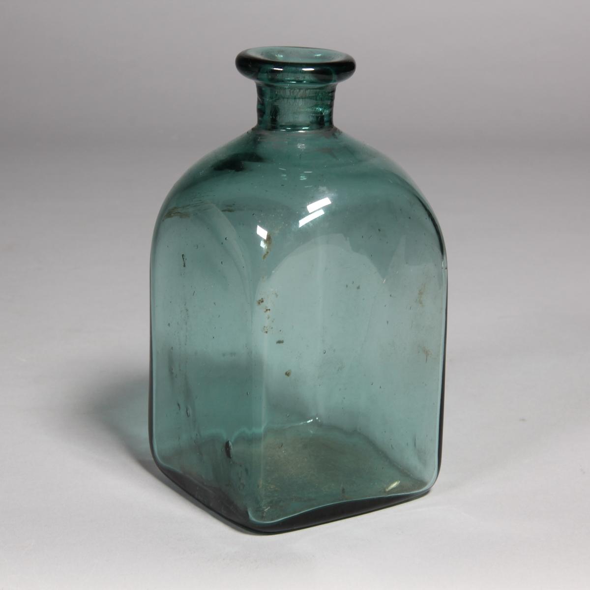 Flaska av grönt glas, kvadratisk med utvikt mynning.