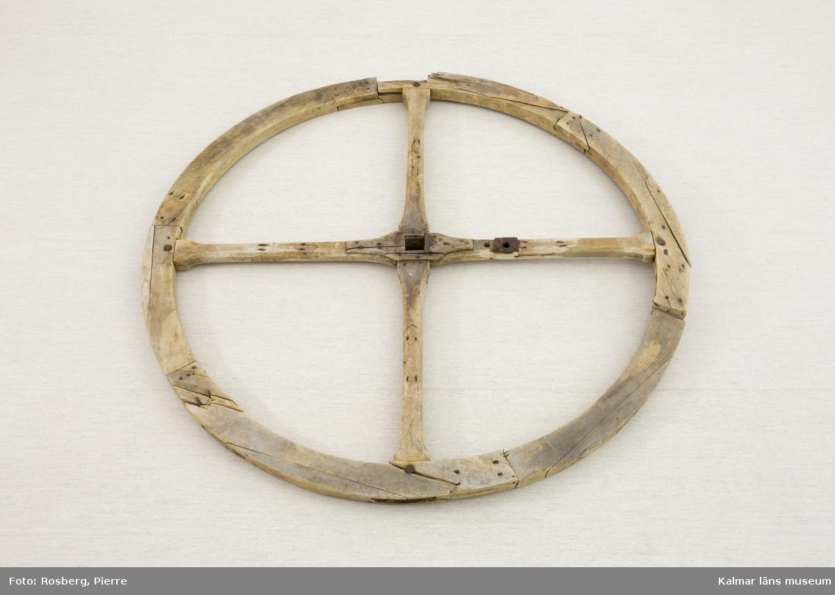 KLM 8823:2. Svänghjul, till maskin. Stort, runt hjul av trä till maskin för pressning av tobak. Infattningar av järn och bly. Två delar av hjulet är lösa. På hjulets ena sida några inristade detaljer, bl.a. ett X och en blomma inom cirkel.