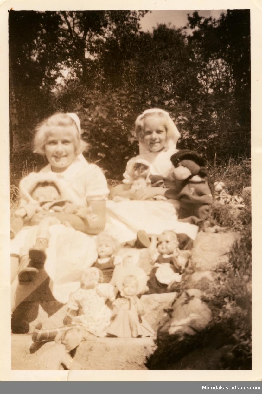 """Berit Gustafsson och Annemarie Berndtsson sitter i trappan med alla deras dockor och nallen """"Jack"""" i trappan utanför ett av husen i """"Stusshålan"""", Kryssgatan i Mölndal. 1945."""
