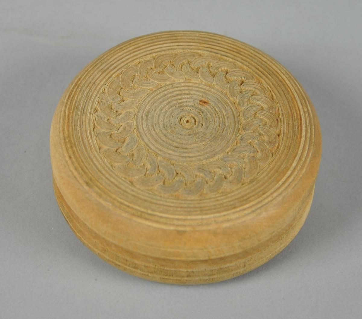 Rund eske av tre, med avtagbart lokk. Esken har innrisset dekor med sirkel- og kjettingmotiv, bunnen har konsentriske sirkler og rutenett.