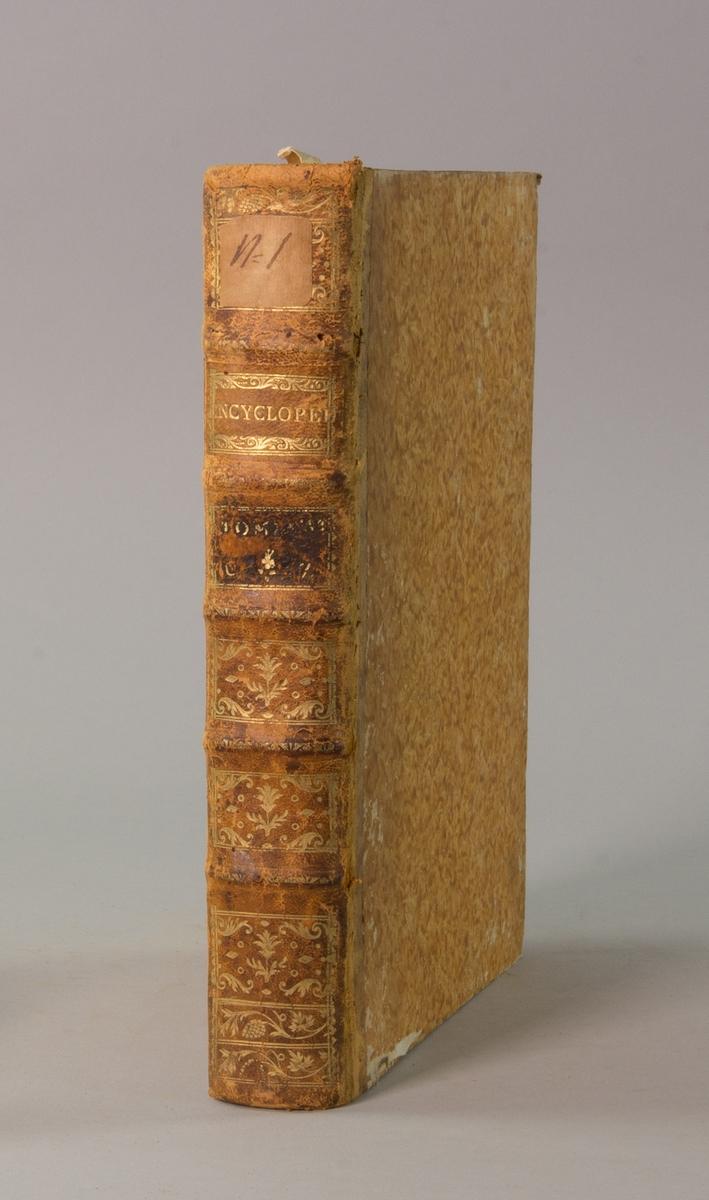 """Bok, """"Encyclopedie ou dictionnaire raisonne des sciences, des arts et des metiers"""" av Diderot och d`Alembert, utgiven 1779. Ny upplaga, vol. 36. Halvfranskt band med pärmar av papp med påklistrat marmorerat papper, rygg av skinn med fem upphöjda bind med guldpräglad dekor, blindpressad och guldornerad rygg, titelfält med blindpressad titel och ett mörkare fält med volymens nummer (närmast utplånat). Med rött snitt. Påklistrad etikett märkt med bläck """"No 1."""""""