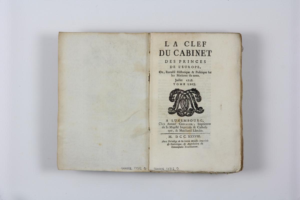 """Bok, pappband """"La clef du cabinet des princes de  l´Europe"""", del 69, tryckt i Luxemburg 1738. Marmorerat band med blekt rygg, påklistrade pappersetiketter med titel och volymens nummer. Med skurna snitt."""