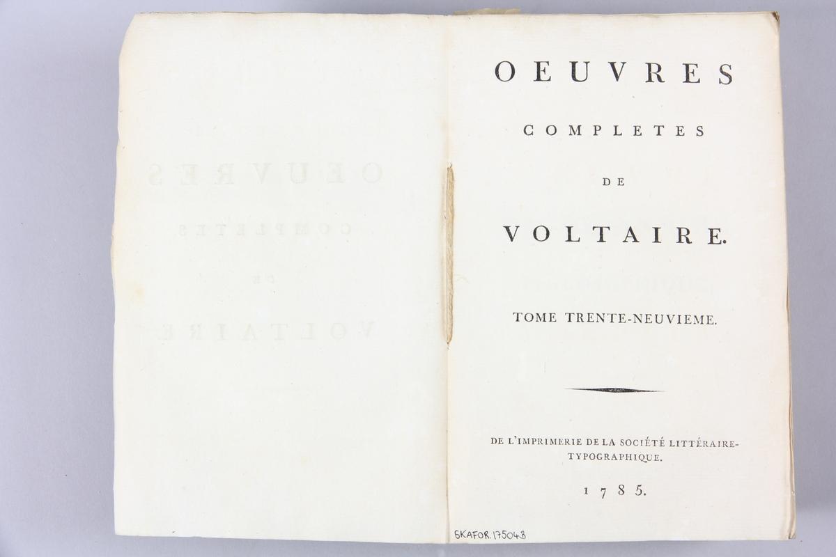 """Bok, pappband, """"Oeuvres complètes de Voltaire."""" del 39, tryckt 1785. Pärm av gråblått papper, skurna snitt. På ryggen pappersetikett med tryckt text med volymens namn och nummer. Ryggen blekt."""