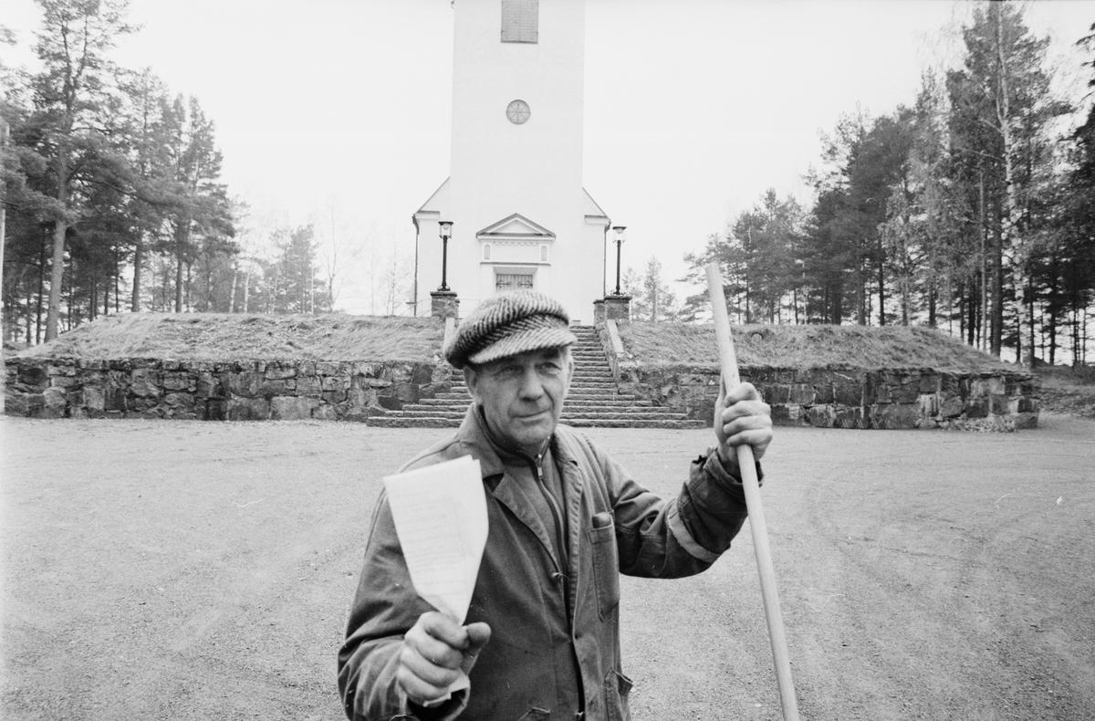 """Man med papper framför kyrka. Bilden är sannolik tagen i samband med reportage om """"Städerska i 13 år på stataravtal"""", Tierp, Uppland"""