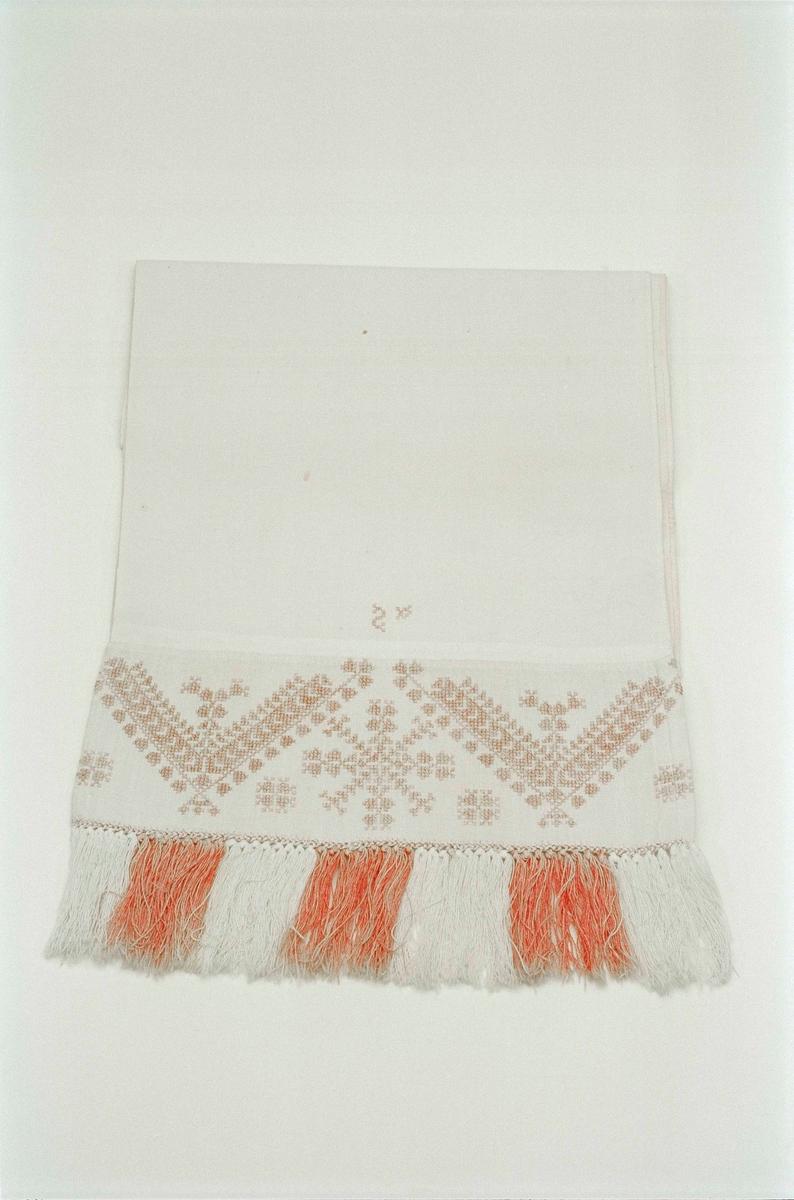 Handkläde av vit bomull, med i rött korsstygnsbroderad bård av halvlinne, knuten frans i rött och vitt. Märkt med ett bakvänt S.