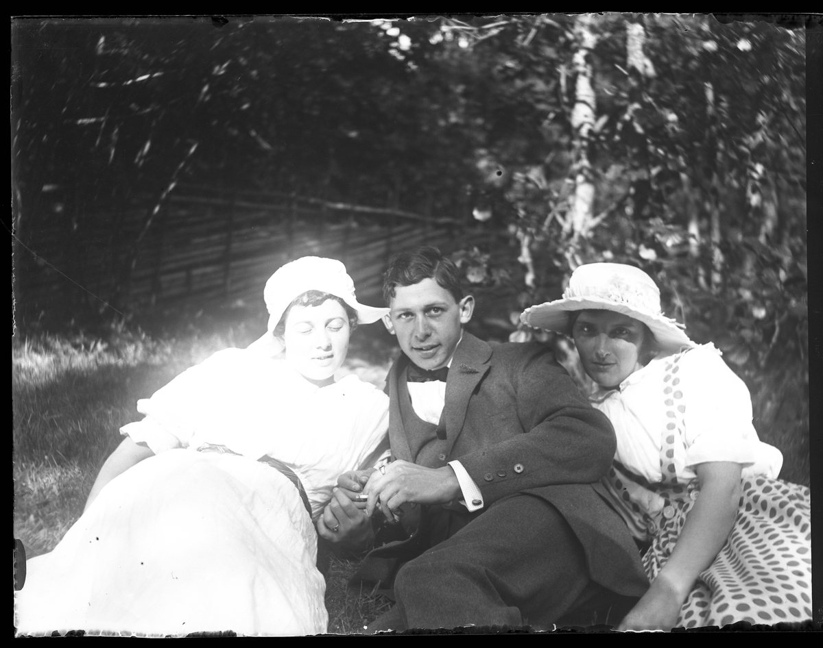 Ella, Hugo Larsson och Ellen fotograferade i Nolhaga. Ella och Ellen är ljust klädda med ljusa hattar. Den ena håller Hugo i handen.