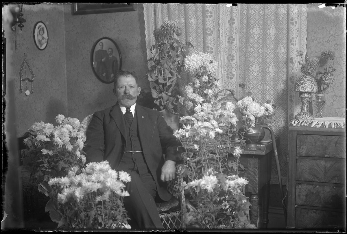 Karl Dahlgren sitter i en korgstol, omgiven av blommor och fotograferad i samband med sin 60årsdag.