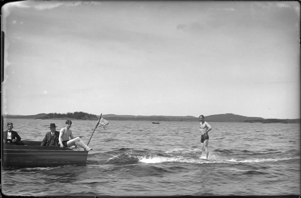 """I en träbåt sitter en man och en pojke, båda kostymklädda. På båtens kant sitter en ung man i badkläder medan en annan man åker bakom båten. I fotografens anteckningar står det """"Surfing, Axelsson""""."""
