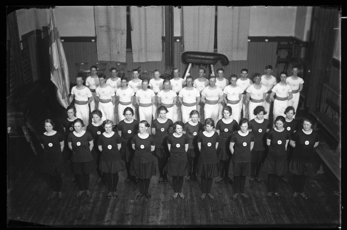 Alingsås Gymnastikförenings (AGFs) trupper uppradade i en gymnastiksal. Männen bär vita dräkter och kvinnorna svarta.
