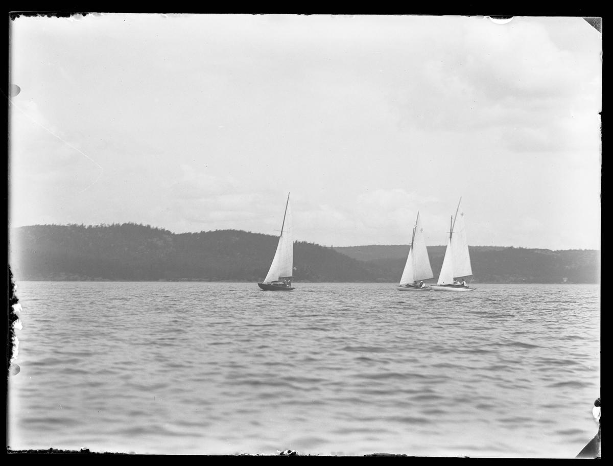 Tre segelbåtar fotograferade i samband med en kappsegling.