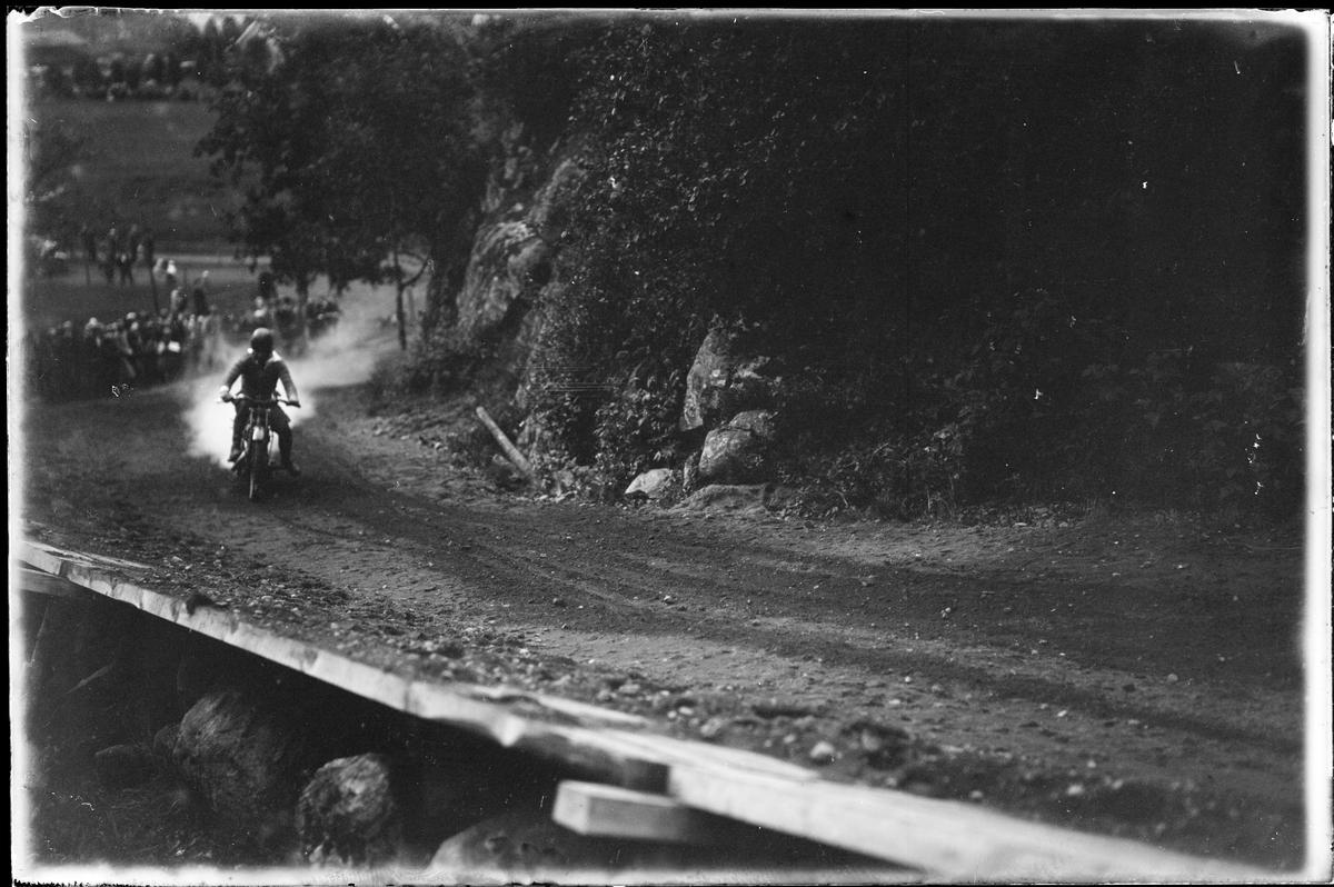 """En person på motorcykel kör upp för en backe. I bakgrunden skymtar åskådare. I fotografens egna anteckningar står det """"A.M.Ks [Alingsås motorklubb] backtävlan"""""""