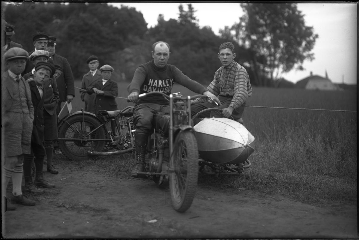 Harald Karlborg fotograferad i samband med Alingsås Motorklubbs backtävlan. Karlborg sitter på en motorcykel med sidovagn, i vagnen sitter en pojke. Bredvid dem står åskådare.
