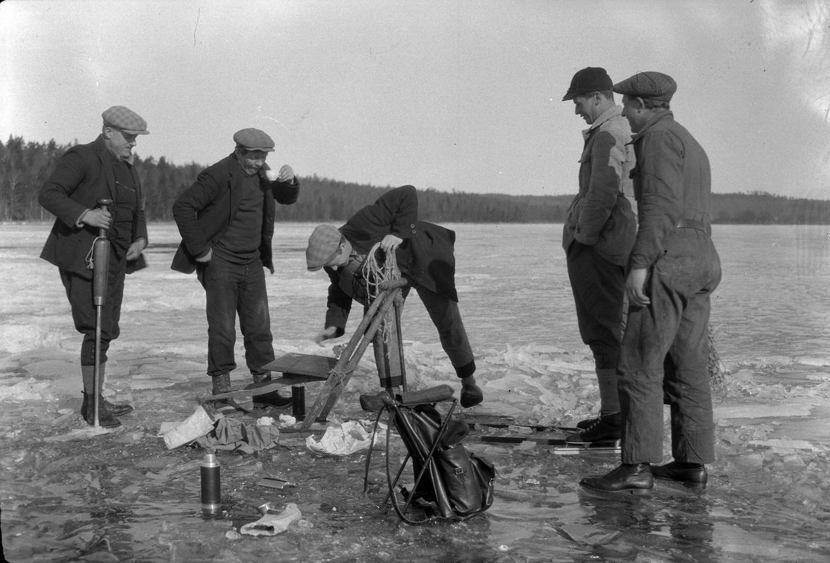 Fem män vinterfiskar och dricker kaffe. Bredvid dem på isen syns en spark, ryggsäckar och en termos.