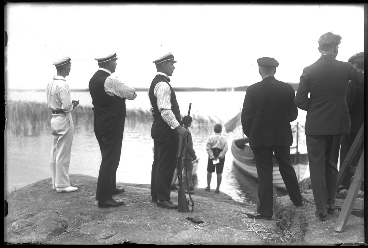 """Ett antal personer står på stranden och tittar på segelbåtar som syns ute till sjöss. I fotografens egna anteckningar står det """"Prisdommarna""""."""